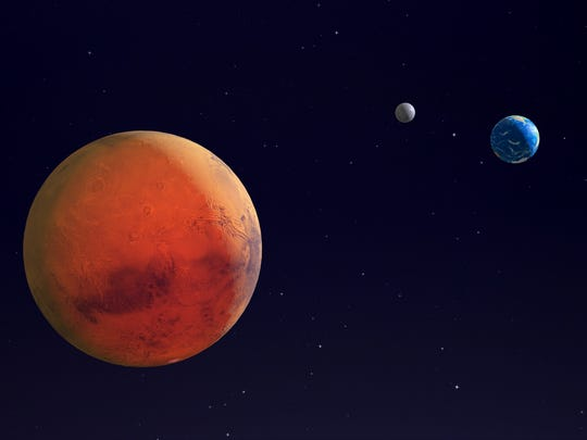 An illustration of Mars with Earth and the Moon in