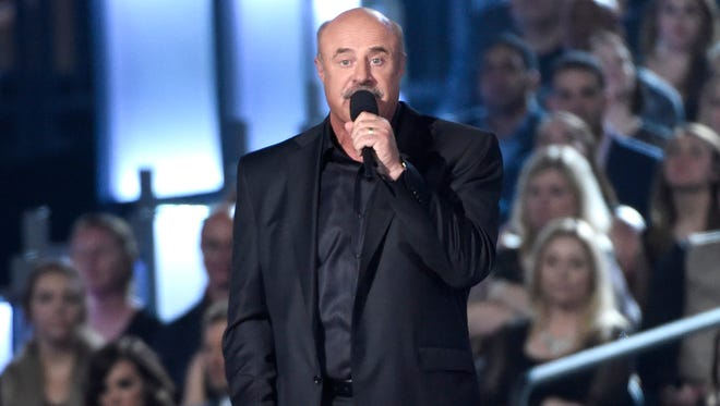 In a Sunday, April 19, 2015 photo, Dr. Phil McGraw speaks on stage at the 50th annual Academy of Country Music Awards at AT&T Stadium, in Arlington, Texas. McGraw and The National Enquirer are lining up for a courtroom brawl after the television talk show host and his wife filed a $250 million lawsuit against the supermarket tabloid and its sister publications, charging that they falsely accused him of being an abusive husband and a hypocrite who doesn't practice what he preaches.