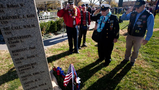 World War II veterans and Pearl Harbor survivors Wardell Jenkins, left, and Lee Warren, second from right, salute after laying a wreath at the base of the Pearl Harbor monument in Vernon Worthen Park during a Pearl Harbor Day memorial remembrance ceremony Friday, Dec. 7, 2012 in St. George, Utah.