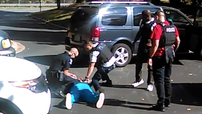In this image taken from video recorded by Keith Lamont Scott's wife, Rakeyia Scott, Tuesday, as Charlotte police squat next to Keith Lamont Scott as Scott lies face-down on the ground. In the video of the deadly encounter between Charlotte police and the black man, Rakeyia Scott repeatedly tells officers her husband is not armed and pleads with them not to shoot him as they shout at him to drop a gun. The video does not show clearly whether Scott had a gun.