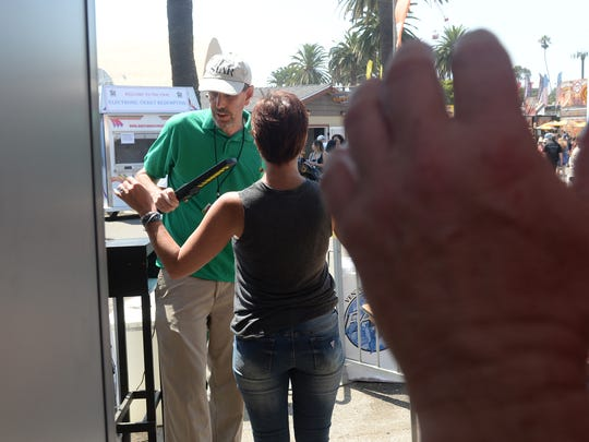 Tom Kisken, Ventura County Star reporter, works with fair personnel and uses a metal-detecting wand at the main entrance of the Ventura County Fair.