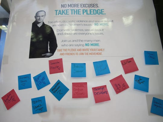Students and others in the El Paso Community College community placed signed sticky notes on a board to show their pledge to help stop domestic violence.