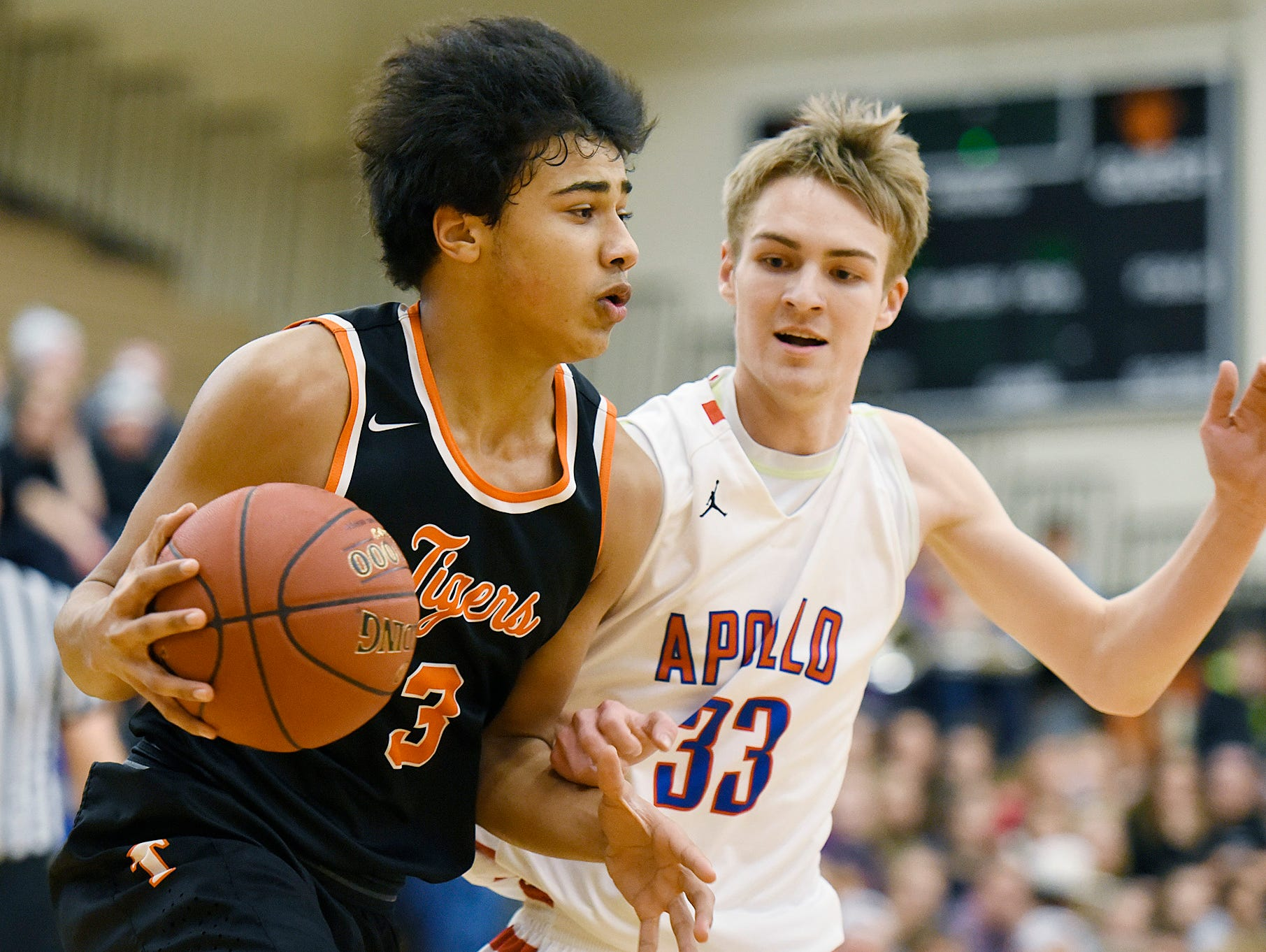 Tech's Brevyn Spann-Ford takes the ball past Apollo's Ben Giese as he drives toward the basket during the first half Tuesday Dec. 8 at Apollo High School.