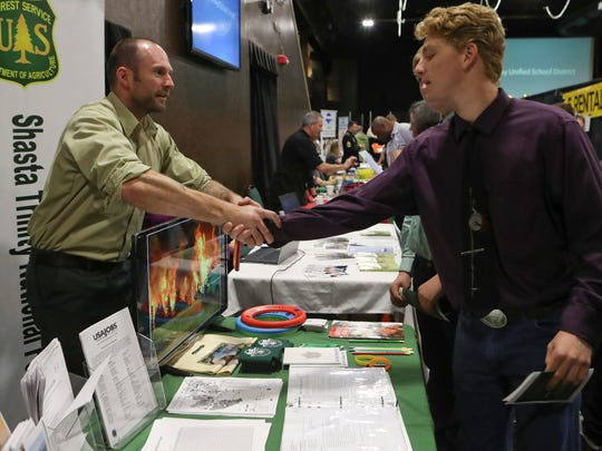 U.S. Forest Service special uses permit administrator Andrew Kennedy, left, talks with Jacob Williams, a junior at California Heritage YouthBuild Academy Thursday during the Smart Center Business Resource Center's Job Fair 2017 at the Win River Resort and Casino.
