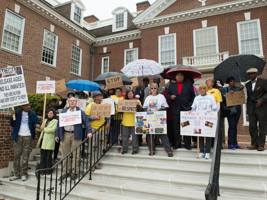 Members of the Journey for Justice: March for Prison Reform hold signs during their rally on the steps of Legislative Hall in Dover.  The group marched from Legislative Hall to the Delaware governor's mansion in Dover on Thursday, May 11, 2017.