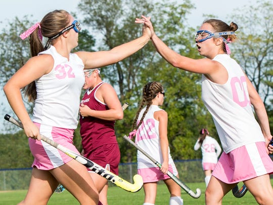 Forbes Road's Mara Broadwater (32) high fives teammate Olivia Hall (00) during a field hockey game against Saint James on Tuesday, Oct. 11, 2016.