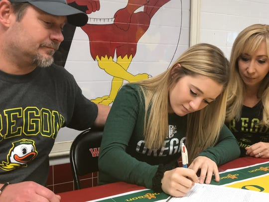 Westwood senior Sara Buchner signs her letter of intent on Wednesday, Nov. 8, 2017 to compete for the University of Oregon acrobatics and tumbling team as her parents, David and Michele, look on.