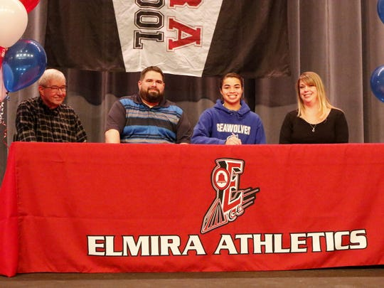 Kendra Oldroyd with her parents, Dan Oldroyd and Christine Saxon, and her grandfather, Richard Oldroyd, at Thursday's signing ceremony at Elmira High School.