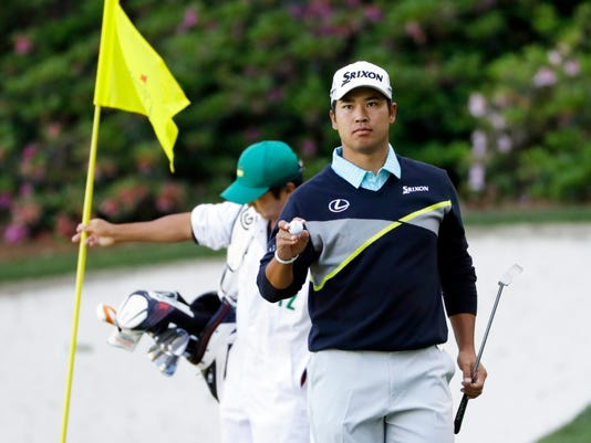 Hideki Matsuyama, of Japan, holds up his ball after putting on the 13th hole during the third round of the Masters golf tournament Saturday, April 9, 2016, in Augusta, Ga. (AP Photo/Matt Slocum)