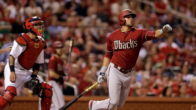 Arizona Diamondbacks' David Peralta, right, and St. Louis Cardinals catcher Yadier Molina watch Peralta's single during the sixth inning of a baseball game Wednesday, May 27, 2015, in St. Louis. St. Louis Cardinals right fielder Jason Heyward was charged with a fielding error and the Diamondbacks scored two runs on the play.