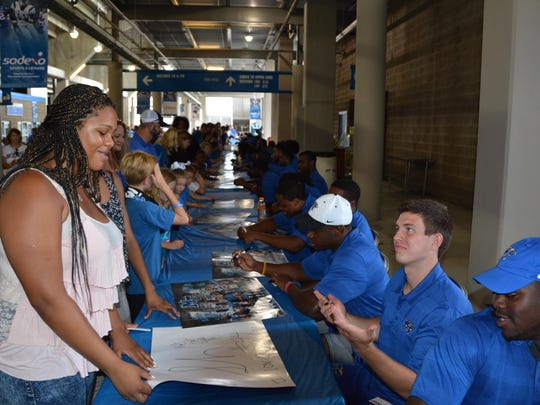 An MTSU fan gets autographs from football players. An estimated crowd of more than 3,000 visitors attended MTSU Fan Day on Sunday.