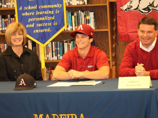 Madeira senior Andrew Benintendi smiles with his Arkansas hat on after signing with the Razorbacks for baseball Nov. 13, 2012. His mother, Jill, is left and father, Chris, is to the right. Benintendi is a four-year starter in both baseball and basketball. He led the CHL in hitting and home runs as a junior and was also CHL and state player of the year in basketball.