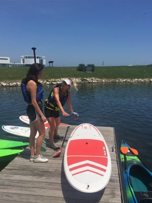 Lily Berlett (right) shows reporter Elena Weissmann how to paddle, kneel and stand on the board before hitting the water.