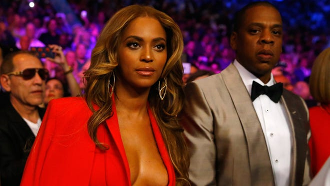 Jay Z and Beyonce while Floyd Mayweather Jr. throws a right at Manny Pacquiao during their welterweight unification championship bout on May 2, 2015 at MGM Grand Garden Arena in Las Vegas, Nevada.