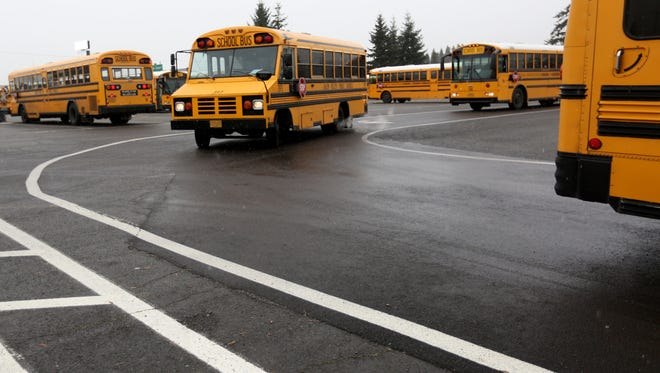 Buses prepare to transport students after the Salem-Keizer School District let out students two hours early because of snow on Wednesday, Dec. 14, 2016.