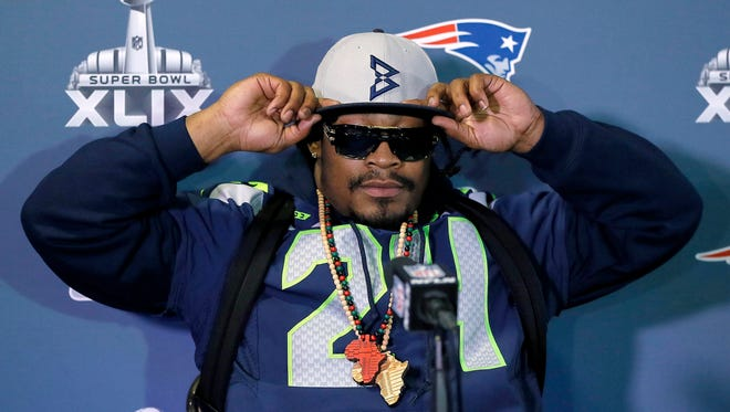 Seahawks' Marshawn Lynch adjusts his cap during an interview for NFL Super Bowl XLIX football game, Thursday, Jan. 29, 2015, in Phoenix.