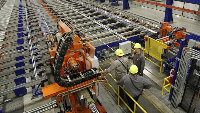 Associates straighten an aluminum extrusion at Nanshan America, 3600 U.S. 52 South in Lafayette. Nanshan America produces aluminum extrusions, casts aluminum billet and constructs various products containing aluminum extrusions.