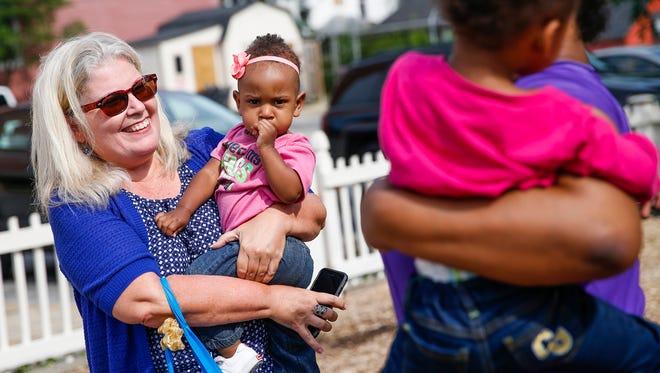 IndyStar reporter Maureen Gilmer holds Olivia, 1, daughter of Adrienne Brown, at Wheeler Mission Center for Women & Children on Wednesday, July 12, 2017.
