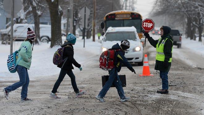 Crossing guard Terrie VanderLoop helps students get across Merrill Street, as Foxview Intermediate School hosts a Walk to School Day event.