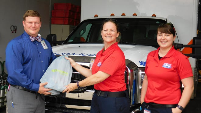 James Perras, emergency preparedness coordinator for Tennova Healthcare – Clarksville, presents Susan Coghill, paramedic, and Meagan Winn, advanced EMT, each with a bag full of treats in honor of EMS Week.