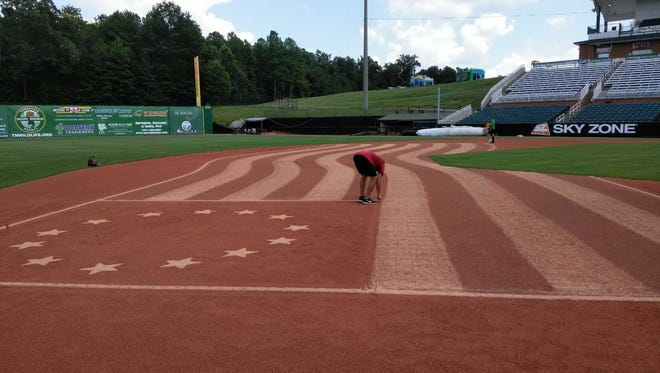 One of the grounds crew workers at The Ballpark at Jackson puts the finishing touches on the waving flag in the infield before Wednesday's game between the Jackson Generals and Tennessee Smokies.