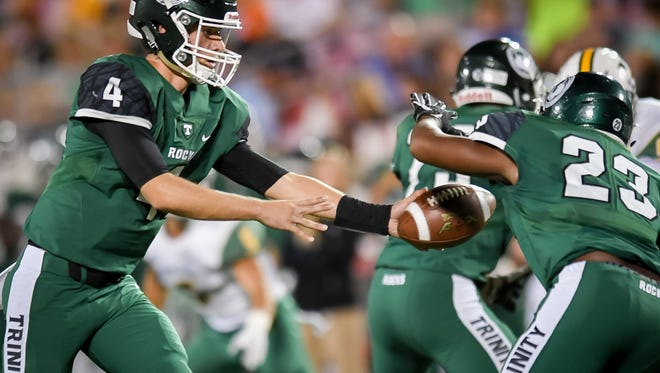 Trinity's Nick John hands the ball off to Geremian Smith during their game played against Saint Xavier at The University of Louisville's Papa John's Stadium in Louisville, Ky, Friday, September 29, 2017.  (Photo Bryan Woolston)