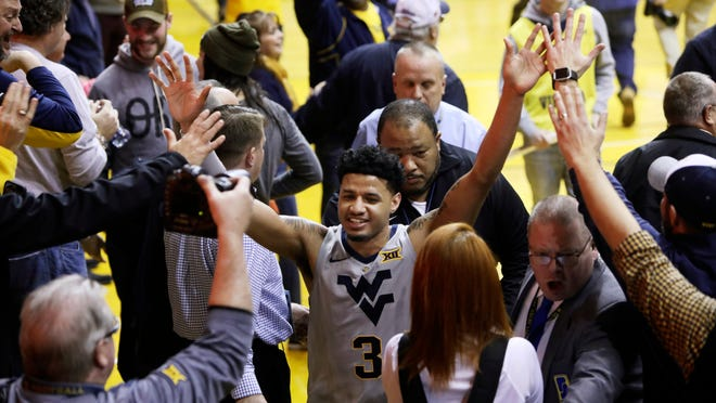 West Virginia guard James Bolden (3) celebrates at the conclusion of an NCAA college basketball game against Kansas Saturday, Jan. 19, 2019, in Morgantown, W.Va. West Virginia defeated Kansas 65-64. (AP Photo/Raymond Thompson)