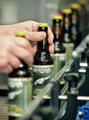 Bottles of Great Basin Co.'s Ichthyosaur Ale come out of the brewery's high-speed bottling machine.