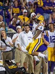 LSU running back Derrius Guice (5) leaps over Missouri safety Thomas Wilson (8) during the first half last season.