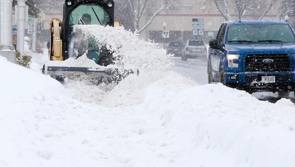 A contruction vehicle plows snow on a sidewalk along