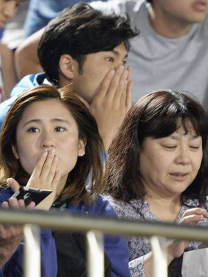 Japanese soccer fans react to a strong earthquake as they watch a J-League soccer match between the Shonan Bellmare and the Sanfrecce Hiroshima at BMW Stadium in Hiratsuka, southwest of Tokyo, May 30, 2015. A powerful and extremely deep earthquake struck a group of remote Japanese islands and shook Tokyo on Saturday, but officials said there was no danger of a tsunami.
