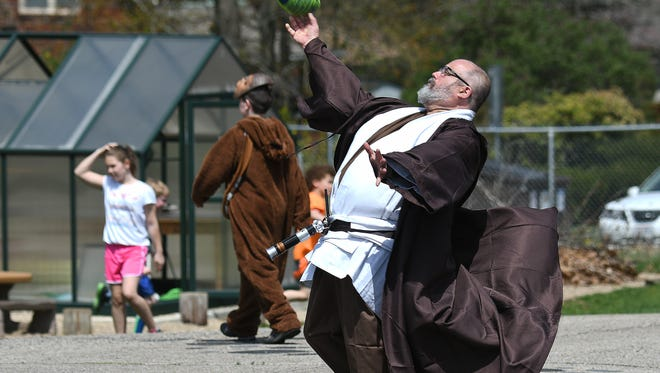Gabe Costa, principal at the Spanish Immersion School, plays football with students at recess dressed as Obi-Wan Kenobi to celebrate May the Fourth day.