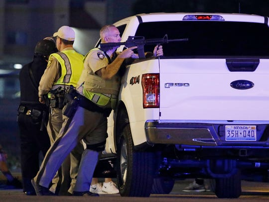 A police officer takes cover behind a truck at the