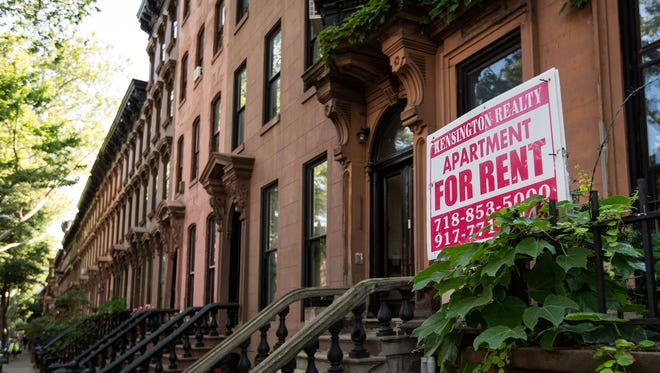 A sign advertises an apartment for rent along a row of brownstone townhouses in the Brooklyn borough of New York City.