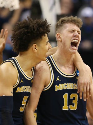 Michigan forwards Moe Wagner, right, and D.J. Wilson celebrate against Louisville during the second half of U-M's 73-69 win March 19 at Bankers Life Fieldhouse in Indianapolis in the second round of the 2017 NCAA tournament.