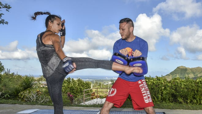 """Tessa Simpson throws a bruising roundhouse kick while her husband, Randy Vera hold the pads in Apra Heights on Nov. 27. """"I like to finish my fights as quickly as possible,"""" said Simpson, as she prepares for PXC 50 on Dec. 4."""