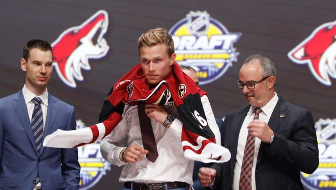 Jakob Chychrun puts on a team jersey after being selected as the number sixteen overall draft pick by the Arizona Coyotes in the first round of the 2016 NHL Draft at the First Niagra Center.
