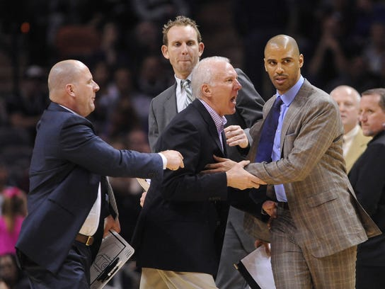 """In this Jan. 17, 2014, file photo, San Antonio Spurs coach Gregg Popovich, middle, is held back by assistant coaches Jim Boylen, left, Sean Marks, top, and Ime Udoka as he argues with officials during second-half NBA action against Portland in San Antonio, Texas. The Brooklyn Nets have hired Sean Marks of the San Antonio Spurs as their general manager. Nets owner Mikhail Prokhorov on Thursday, Feb. 18, 2016, lauded Marks for his coaching and management experience, saying it """"gives him a 360-degree view of the job at hand.""""(Bill Calzada/San Antonio Express-News via AP)"""