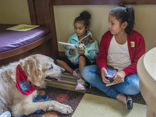 Sisters, Alicia Martinez, 8, and Mina Powell, 6, have fun reading to Jack a 10-year-old therapy dog at the Delta Township District Library as part of Paws for Reading Saturday.