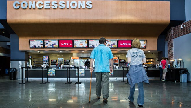 Customers walk to the concessions stand at the Penn Cinema Riverfront IMAX before the start of a movie on Monday afternoon. The theater will soon begin selling beer and wine.