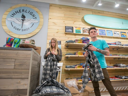 Kristina Mikul, left, and Alex Gossman fold new merchandise Dec. 22 at the Innerlight Surf Shop's new location on Palafox Place in downtown Pensacola.