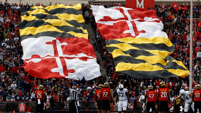 Fans hold a Maryland flag in the first half of an NCAA college football game between Maryland and Penn State in College Park, Md., on Nov. 25.