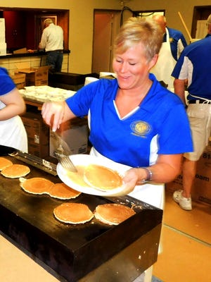 Fremont Kiwanis Club member Betsy Sweeney grills up a plate of pancakes at 7 a.m. Wednesday.