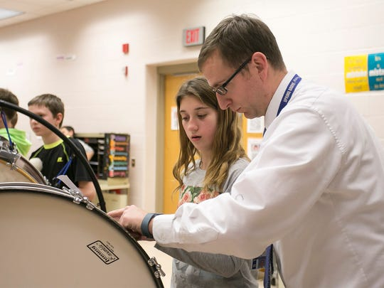 "Spring Grove Intermediate School Band Director Tim Bupp helps fifth-grader Carly Esaley, during band practice Wednesday, March 16, 2016. The fifth- and sixth-grade band, will play ""Tears of Arizona"" publicly for the first time during a concert, held at the school on March 31, and then again in Washington D.C in May. Amanda J. Cain photo"