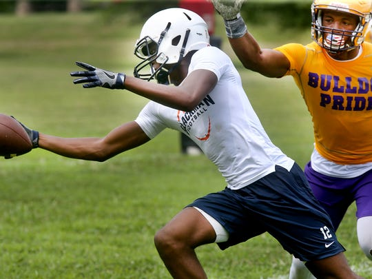 Blackman's Amir Frazier runs the ball during Riverdale High school's annual 7-on-7 passing tournament at the school as Smyrna's Casey Perkins comes up from behind Frazier, on Thursday July 14, 2016.