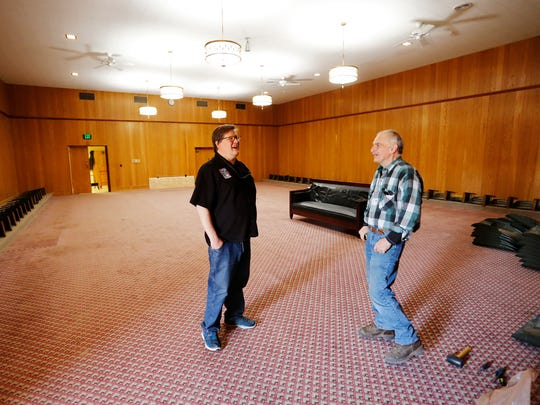 Craig Hadley, executive director of Tippecanoe County Historical Association (TCHA), shares a laugh with Jerry Day inside the auditorium Thursday, April 12, 2018, of the former Masonic Temple at the corner of Sixth and Columbia streets in downtown Lafayette. The TCHA purchased the building in January of 2017. The TCHA is renovating the building and will offer it as an event venue and also use it for curatorial space. Day, who was replacing the cushions on original stadium chairs in the auditorium, formerly served as operations manager, assistant director and interim director of the TCHA.