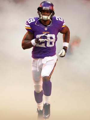 Minnesota Vikings running back Adrian Peterson (28) runs onto the field through a cloud of smoke before the game against the Pittsburgh Steelers in the NFL International Series game at Wembley Stadium.