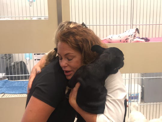 Pet store spokeswoman Linda Nofer hugs Glendale police Detective Beth Diaz, who worked on the case to find the stolen puppy, on July 26, 2018.
