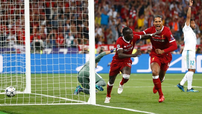 FILE - In this Saturday, May 26, 2018 file photo, Liverpool's Sadio Mane, left, celebrates scoring his side's first goal during the Champions League Final soccer match between Real Madrid and Liverpool at the Olimpiyskiy Stadium in Kiev, Ukraine. Mane, who left a rural village in southern Senegal as a teenager to find international stardom in Europe, hopes to defy the odds again at the World Cup in Russia. (AP Photo/Matthias Schrader, File)