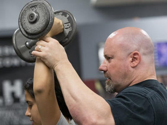 Tim Sparkes, owner of Die Hard Gym and Fitness, trains Nadia Vasquez, 14, of Phoenix, at his Peoria gym.